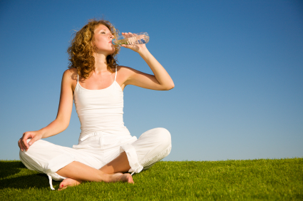 Young woman sitting on grass and drinking water